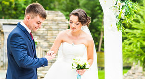 Bride slipping ring on finger of groom at wedding Royalty Free Stock Image
