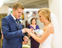 Bride slipping ring on finger of groom at wedding Royalty Free Stock Photos