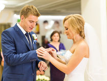 Bride slipping ring on finger of groom at wedding Stock Images