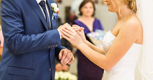 Bride slipping ring on finger of groom at wedding.  Royalty Free Stock Image