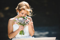 Bride Smelling Bouquet. Bride smelling wedding bouquet at windy sunny day Royalty Free Stock Photo