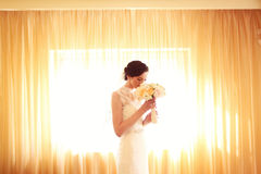 Bride smelling flowers. Beautiful Bride smelling flowers in sunlight Stock Image