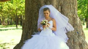 Bride Smelling Flowers Under A Tree stock video