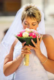 Bride smelling wedding bouquet Stock Photo