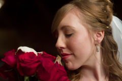 Bride Smells Bouquet. A close up image of a bride smelling her rose and calla lily bouquet. Her eyes are closed and she looks radiant royalty free stock photography