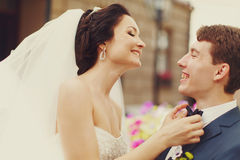 Bride smiles adjusting groom's blue bow tie Royalty Free Stock Photography