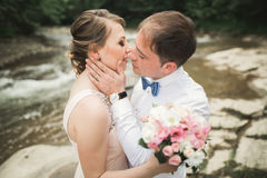 Bride smiles with closed eyes while groom touches her face delicately Royalty Free Stock Photo