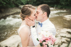 Bride smiles with closed eyes while groom touches her face delicately Stock Images