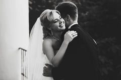 Bride smiles while groom hugs her on the balcony Stock Images