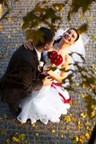 Bride smiles holding a fiance's neck and standing under an autum Royalty Free Stock Photo