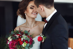 Bride smiles while looking at fiance before a kiss. A Stock Photography