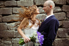 Bride smiles looking at a groom while wind blows her hair Royalty Free Stock Images