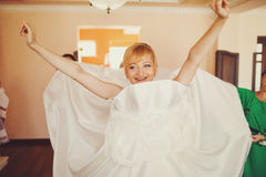 Bride smiles putting on a wedding dress Stock Photo