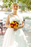Bride smiles standing with a bouqet on a street in shiny morning royalty free stock images