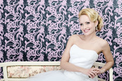 Bride smiling sitting bench. 20s yeared bride in white wedding dress is sitting on a bencs hear the colorful wall Royalty Free Stock Photos