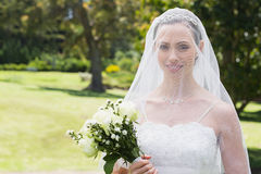Bride smiling through veil in garden Stock Photos