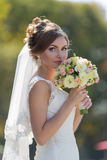 Bride sniffs bridal nosegay looking at camera. Waist up portrait of bride with bouquet in park. Attractive bride sniffs bridal nosegay on open air looking at stock image
