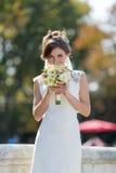 Bride sniffs bridal nosegay on open air Royalty Free Stock Photos