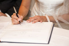 Wedding signature. Bride on solemn write on registration of marriage in the Wedding Royalty Free Stock Photography
