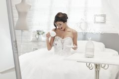 Bride spilling coffee on wedding dress Royalty Free Stock Image