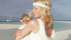 Bride Spinnning Bridesmaid Around At Beach Wedding Stock Photo
