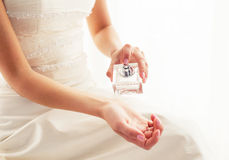 Bride spraying perfume. On her hand Royalty Free Stock Images