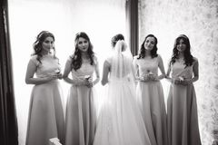 Bride stand back to camera. Bridesmaid hold bouquets in hands. They stay in front of window royalty free stock photo