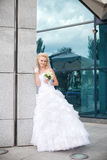 Bride stand at a column of the building and reflection in glass Royalty Free Stock Image