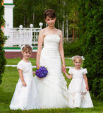 Bride stand with two little girls - bridesmaid. Bride stand with little girls in elegant dresses Stock Image