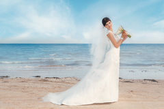 Bride standing by the beach Royalty Free Stock Photography