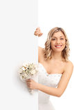 Bride standing behind a blank panel Royalty Free Stock Images