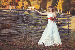 Bride standing with bouquet near the wicker fence. Beautiful bride in an elegant dress standing with bouquet near the wicker fence in autumn park Stock Image