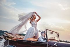 Bride standing in classic convertible while being driven. By older driver royalty free stock photos