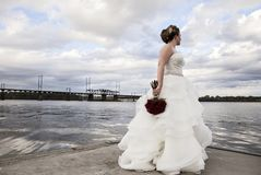 Bride standing on dock. A bride standing on a dock on edge of river holding bouquet of red roses Royalty Free Stock Photos