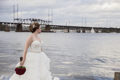 Bride standing on dock. A bride standing on a dock on edge of river holding bouquet of red roses Royalty Free Stock Image