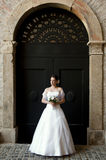 Bride standing in front of a black arch gate. Royalty Free Stock Images
