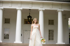 Bride standing in front of pillared porch Royalty Free Stock Photos