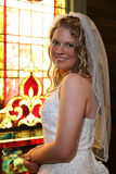 Bride standing in front of stained glass window Royalty Free Stock Image