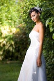 Bride standing in garden. In white gown Stock Photo