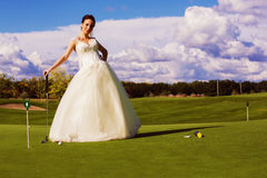 Bride standing on golf field Royalty Free Stock Photos