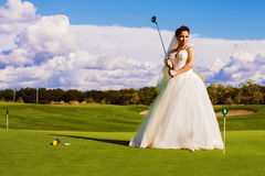 Bride standing on green golf field Royalty Free Stock Images