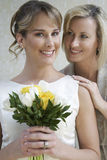 Bride Standing With Her Mother. Portrait of pretty bride holding bouquet while mother standing by Stock Photos