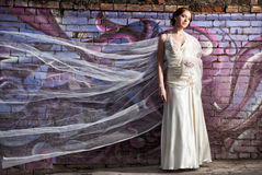 Bride standing near colorful wall with flying veil Stock Photo