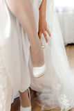 The bride standing on one leg and the second leg pulled a white Royalty Free Stock Photo