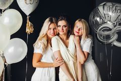 Bride standing with sad bridesmaids and showing wedding rind stock image