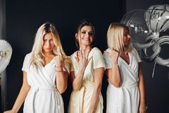 Bride standing with sad bridesmaids and showing wedding rind
