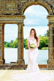 Bride standing by stone arch and lake Royalty Free Stock Images