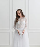 Bride standing with wedding accessories. In white room Stock Images