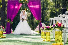 Bride standing in wedding archway with chairs on on each side Royalty Free Stock Images