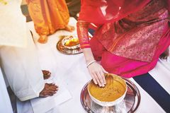 Women preparaing for pasting the turmeric haldi oil mixed with milk on bride`s feet and body. The bride standing on the white fabric and the women prepraing the Stock Photo